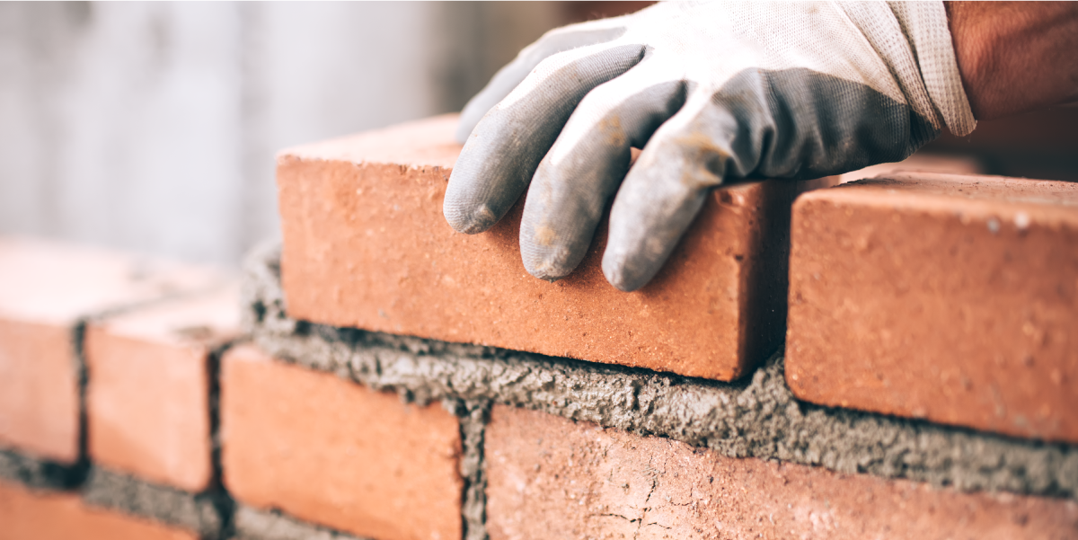 Image of Person Laying Bricks to Metaphorically Represent Building a Foundation of Financial Confidence