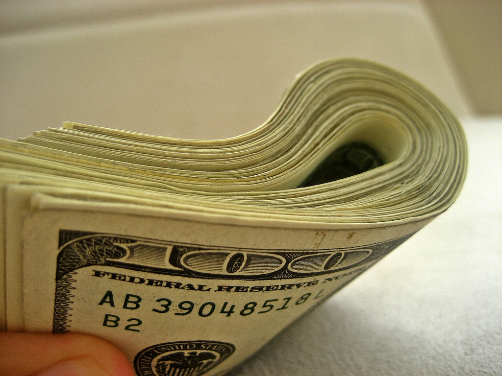 Stack of hundred dollar bills illustrates article on small business tax penalty
