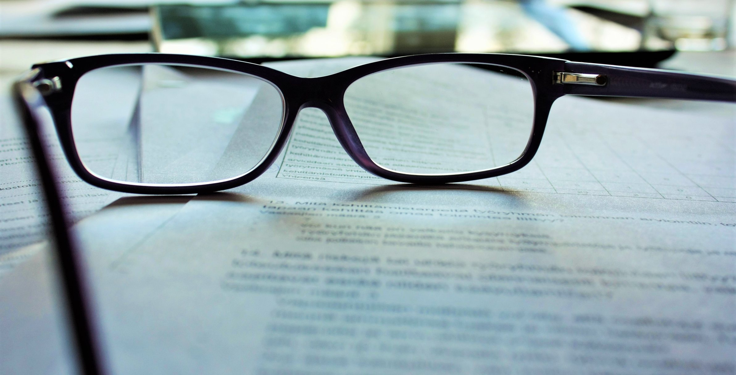 Photo of glasses and papers illustrates article on what small business owners need to outsource accounting.