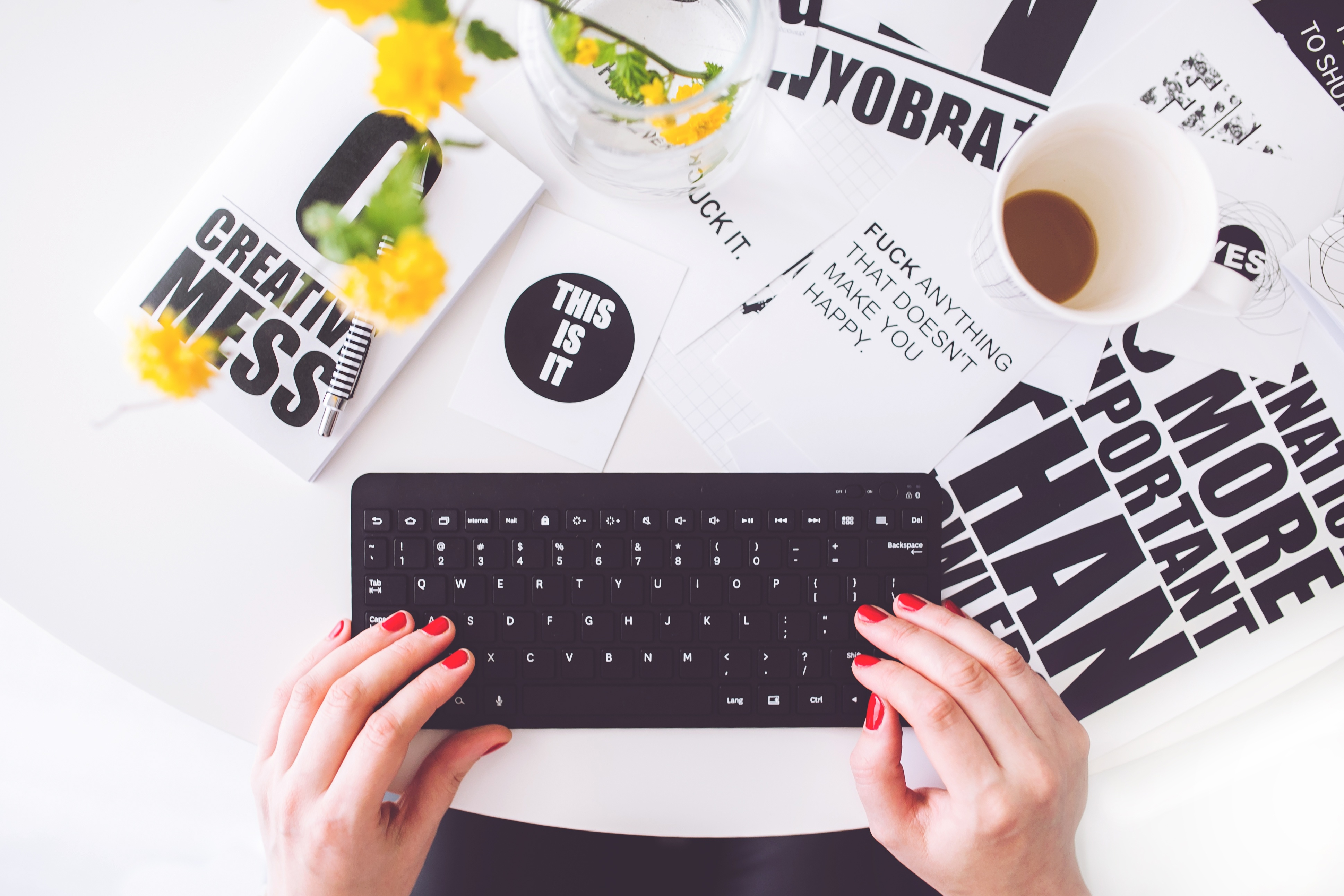 woman at keyboard surrounded by print materials illustrates article on small businesses finding and hiring freelancers